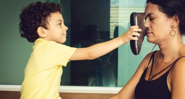kid putting smelly shoes in mom's face