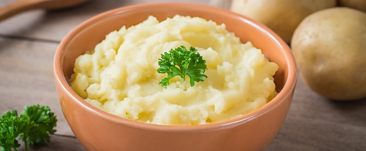 Bowl of mashed potato with garnish on the top and whole potatoes on the side. There is also a spoon in the background.