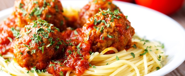 Spaghetti and meatballs in a bowl on a brown table with three ripe tomatoes behind the bowl.