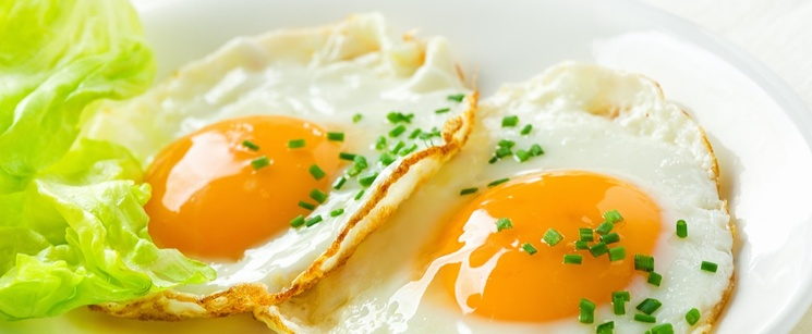 Two sunny side up eggs on a plate.