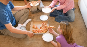 family eating pizza on the floor