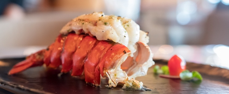 Cooked Lobster tail with meat coming out of the shell.