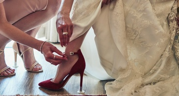 bridesmaid helping to dress bride