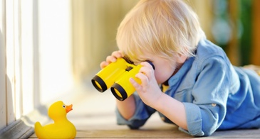 little boy using binoculars looking at rubber duck