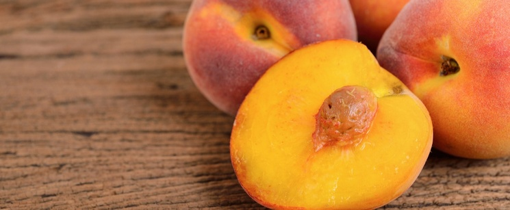 Four ripe peaches, one with a slice down the middle on a brown table.