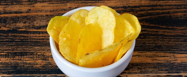 Small bowl of golden potato chips.