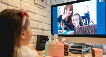 little girl celebrating birthday on video call with cake