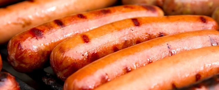 Multiple hot dogs on the grill with grill marks on the hot dogs.