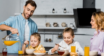 family having breakfast orange juice cereal